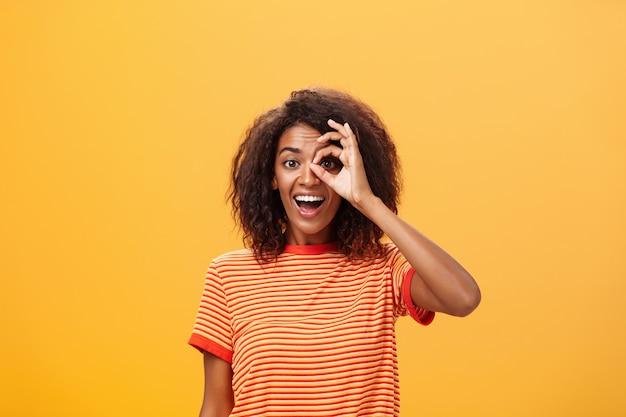 Fille adulte à la peau foncée avec une coiffure frisée en tshirt rayé montrant un cercle sur les yeux ou un geste correct sur le mur orange