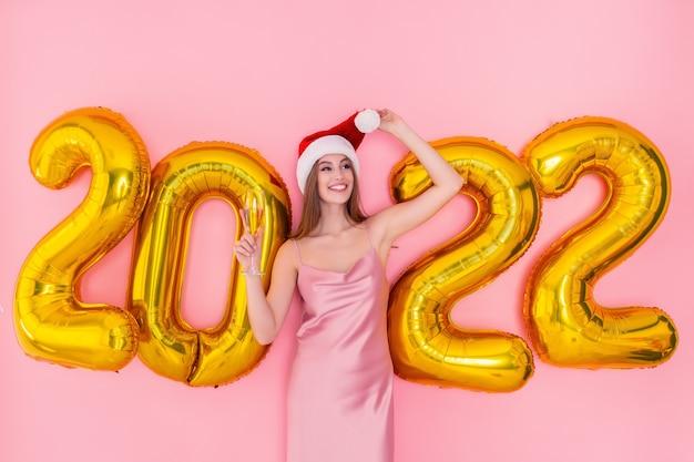 Une fille adulte souriante tient une coupe de champagne dans un concept de nouvel an de ballons à air doré de chapeau de père noël