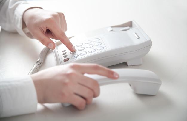 Fille d'affaires appelant au téléphone de bureau.