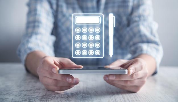 Fille d'affaires tenant l'icône de stylo et calculatrice.