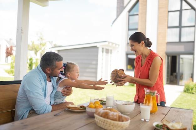 Fille affamée. jolie jolie fille prenant un bol avec des biscuits ayant faim le matin