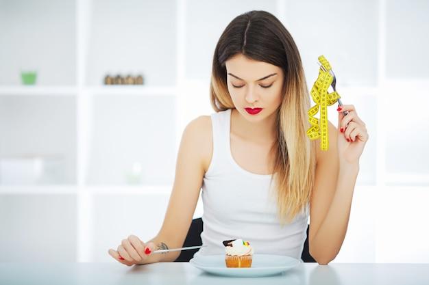 Fille affamée avec un ruban à mesurer jaune tient dans la main à la recherche de gâteau cupcake en assiette.