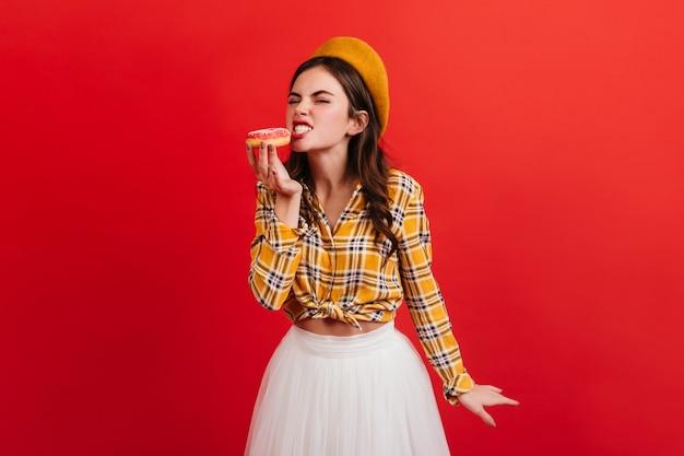 Fille affamée en tenue élégante mord le beignet aux fraises. portrait de femme en chemisier à carreaux et béret orange sur un mur lumineux.
