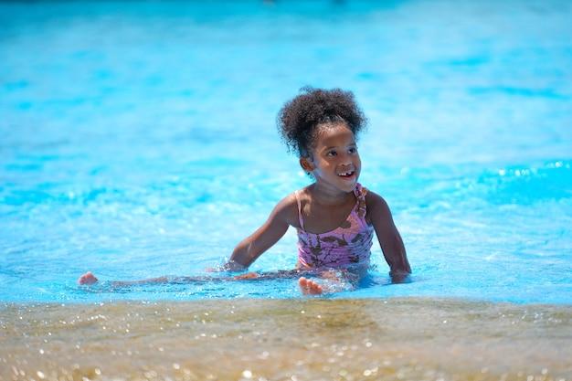 Fille africaine assise et jouant de l'eau dans la piscine du parc d'attractions.