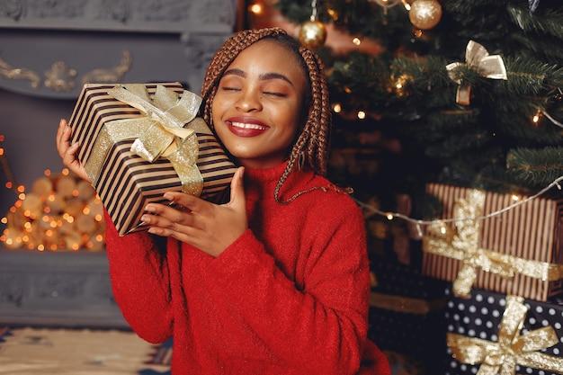 Fille africaine dans une décoration de noël / femme dans un pull rouge. concept de nouvel an.