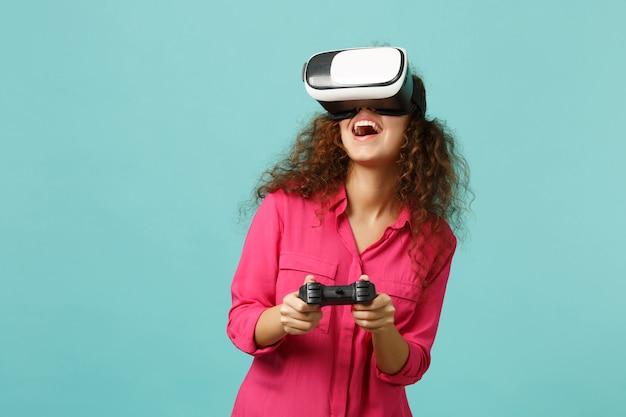 Fille africaine drôle dans des vêtements décontractés regardant dans un casque, jouant à un jeu vidéo avec une manette isolée sur fond de mur bleu turquoise. les gens émotions sincères, concept de style de vie. maquette de l'espace de copie.