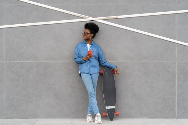 Une fille africaine élégante avec un smartphone tient une conversation de jeune femme décontractée à la mode sur un longboard sur un téléphone portable