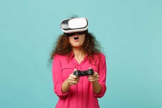 Fille africaine étonnée dans des vêtements décontractés regardant dans un casque, jouant à un jeu vidéo avec un joystick isolé sur un fond de mur bleu turquoise. les gens émotions sincères, concept de style de vie. maquette de l'espace de copie.