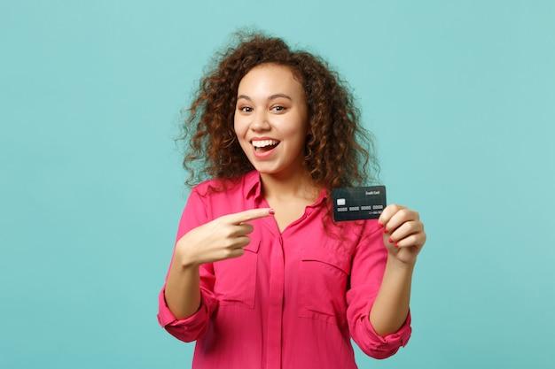 Une fille africaine excitée en vêtements décontractés roses pointe l'index sur une carte bancaire de crédit isolée sur fond de mur bleu turquoise en studio. les gens émotions sincères, concept de style de vie. maquette de l'espace de copie.