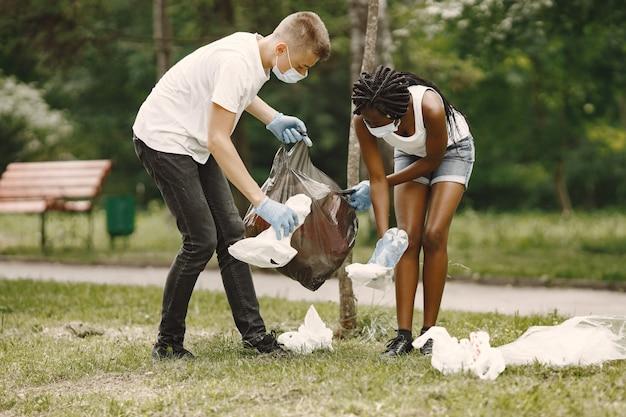 Fille africaine et garçon européen ramassant des ordures. des militants nettoient le parc sur le côté.