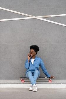 Une fille africaine joyeuse parle au cours d'une conversation téléphonique heureuse souriante s'assoit à l'extérieur sur un longboard