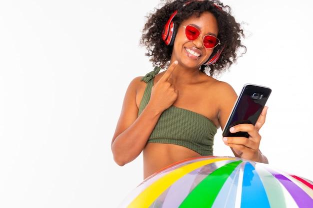Fille africaine en lunettes de soleil et un maillot de bain tient le téléphone dans ses mains et écoute de la musique