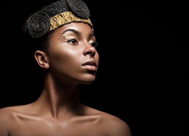 Fille africaine avec maquillage lumineux et accessoires créatifs en or sur la tête.