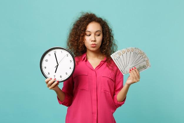 Une fille africaine pensive en vêtements roses tient un ventilateur d'horloge ronde d'argent en billets de banque en dollars en argent comptant isolé sur fond bleu turquoise. les gens émotions sincères, concept de style de vie. maquette de l'espace de copie.