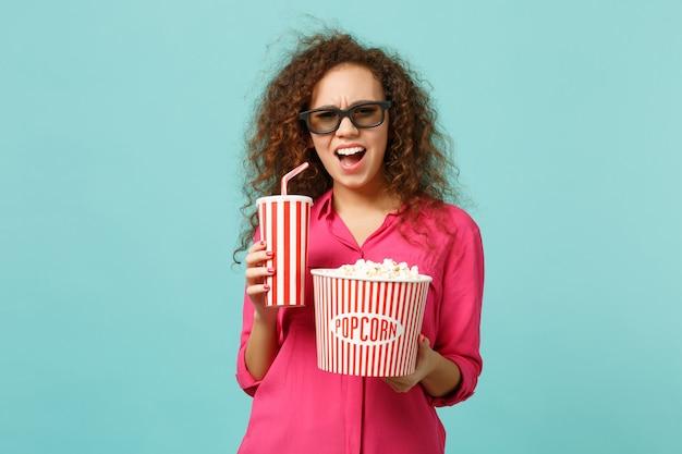 Une fille africaine perplexe dans des lunettes imax 3d regardant un film tient une tasse de pop-corn de soda isolée sur fond bleu turquoise en studio. les émotions des gens dans le concept de style de vie de cinéma. maquette de l'espace de copie.