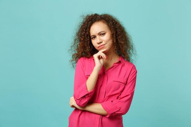 Une fille africaine perplexe et pensive dans des vêtements décontractés à la recherche d'une caméra, mettez la main sur le menton isolée sur fond bleu turquoise en studio. les gens émotions sincères, concept de style de vie. maquette de l'espace de copie.