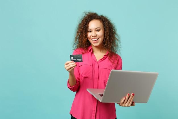 Fille africaine souriante dans des vêtements décontractés à l'aide d'un ordinateur portable tenant une carte bancaire de crédit isolée sur fond bleu turquoise en studio. concept de mode de vie des émotions sincères des gens. maquette de l'espace de copie.