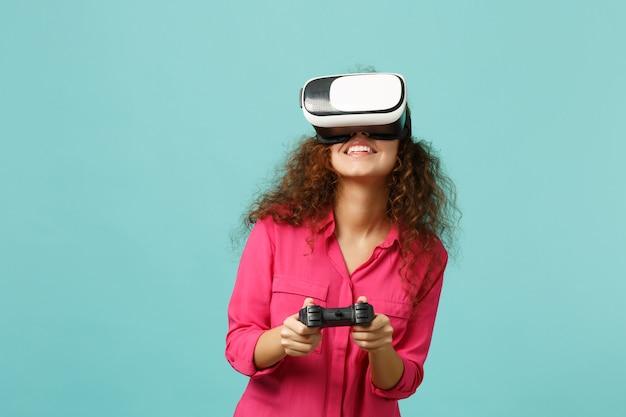 Fille africaine souriante dans des vêtements décontractés regardant dans un casque, jouant à un jeu vidéo avec une manette isolée sur fond de mur bleu turquoise. les gens émotions sincères, concept de style de vie. maquette de l'espace de copie.
