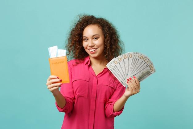 Une fille africaine souriante tient un passeport pour un billet d'embarquement fan d'argent en billets de banque en dollars en espèces isolé sur fond bleu turquoise. concept de mode de vie d'émotion sincère de personnes. maquette de l'espace de copie.