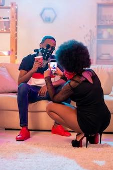Fille africaine en tenue noire assise sur des squats et prendre une photo de son petit ami avec un verre assis sur un canapé moelleux dans le salon