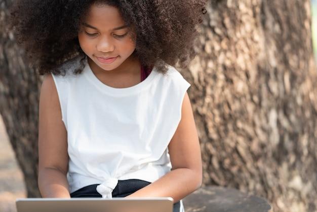 Fille afro-américaine à l'aide d'un ordinateur portable sous l'arbre dans le parc