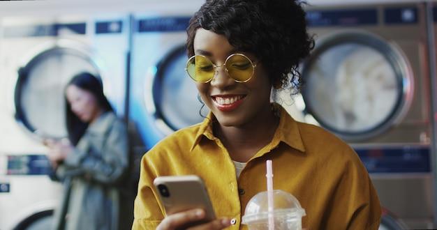 Fille afro-américaine, boire du jus d'orange avec de la paille, envoyer un sms sur le téléphone et attendre que les vêtements soient propres femme sirotant un verre dans la buanderie et tapotant ou faisant défiler sur smartphone