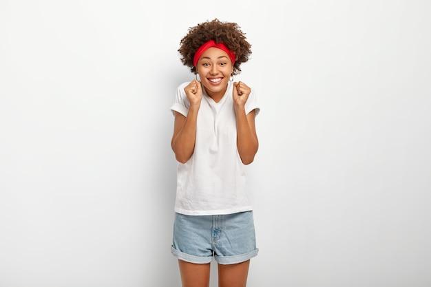 Une fille afro-américaine chanceuse serre les poings, croit en la victoire, sourit joyeusement, montre des dents blanches, vêtue de vêtements décontractés, pose à l'intérieur, se sent comme gagnante, applaudit seul