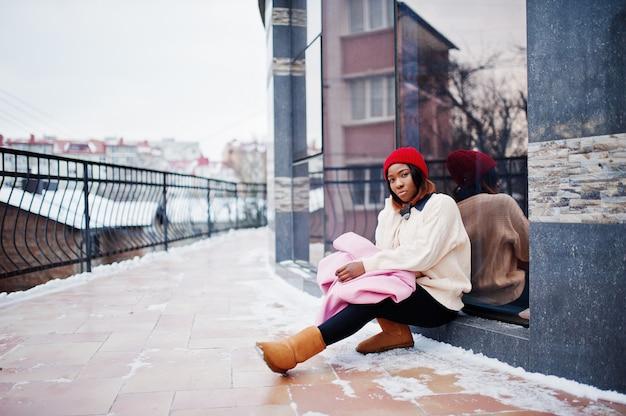Fille afro-américaine en chapeau rouge et manteau rose dans la rue de la ville contre la construction le jour de l'hiver.