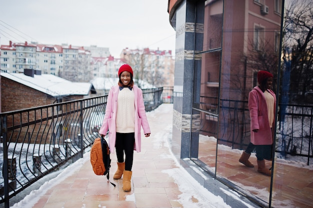 Fille afro-américaine en chapeau rouge et manteau rose avec sac à dos dans la rue de la ville contre la construction le jour de l'hiver.
