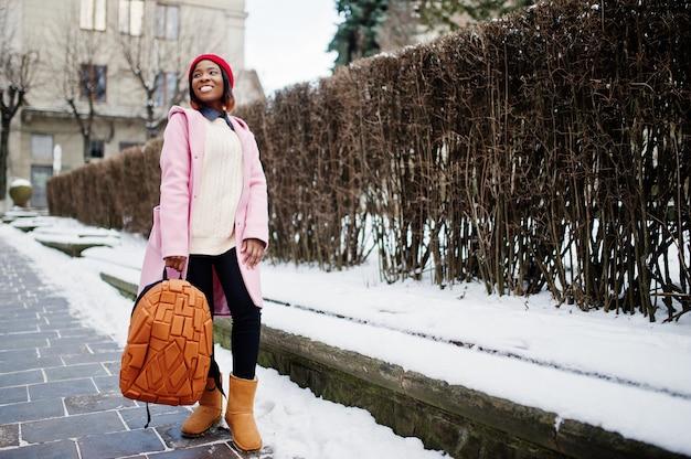 Fille afro-américaine en chapeau rouge et manteau rose avec sac à dos dans la rue de la ville le jour de l'hiver.