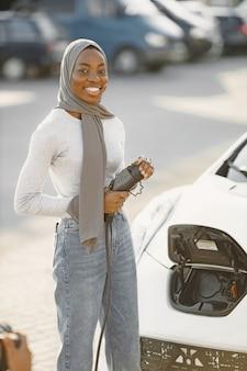 Fille afro-américaine chargeant une voiture électrique à la station-service électrique