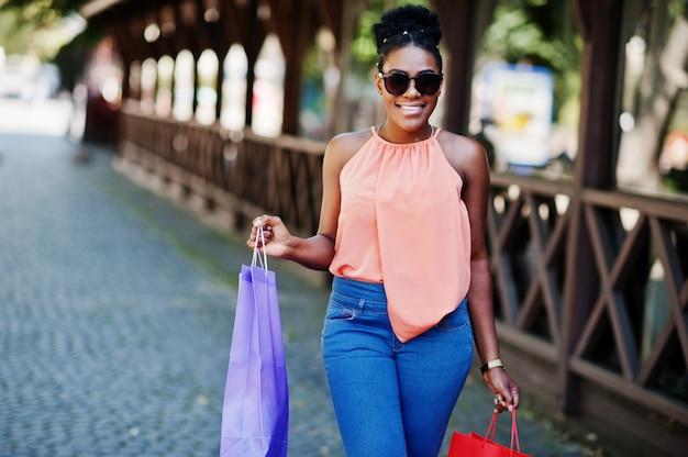Fille afro-américaine décontractée avec des sacs colorés marchant en plein air. femme noire élégante shopping.