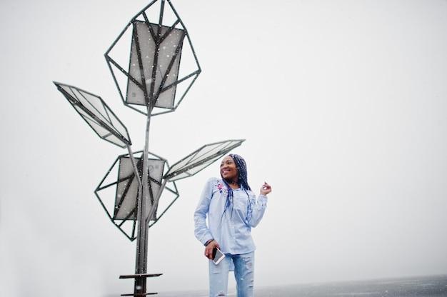 Fille afro-américaine élégante avec des dreads tenant le téléphone mobile à portée de main, en plein air contre les batteries solaires par temps de neige.