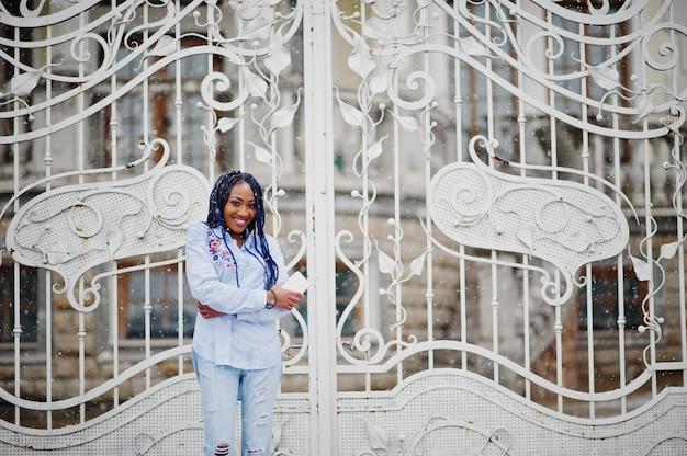 Fille afro-américaine élégante avec des dreads tenant le téléphone portable à portée de main, en plein air contre les portes royales blanches par temps de neige.