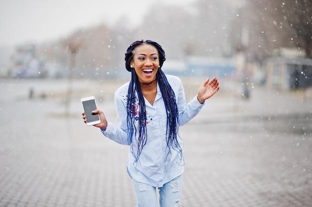 Fille afro-américaine élégante avec des dreads tenant le téléphone portable à portée de main, en plein air par temps de neige.