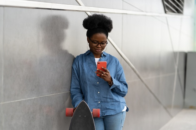 Une fille afro-américaine envoie des sms ou navigue dans une application pour smartphone à l'extérieur, utilise une connexion internet g