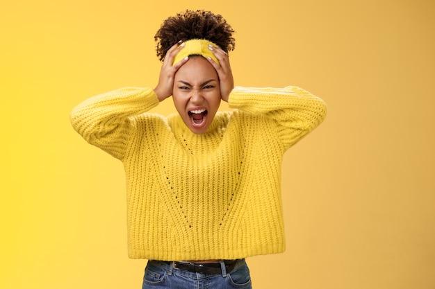 Une fille afro-américaine furieuse, furieuse et énervée, devient folle, crie un regard agressif, agacée, marre de toucher la tête, grimaçant, effrayante, dangereuse, très stressée, fond jaune.