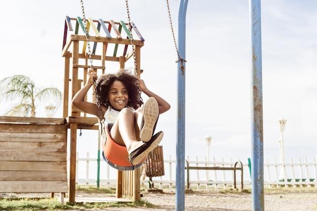 Fille afro-américaine heureuse et souriante jouant sur la balançoire. concept d'amusement et de loisirs. espace de copie
