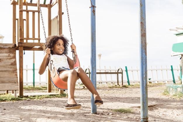 Fille afro-américaine heureuse et souriante jouant sur la balançoire. concept d'amusement et de loisirs.