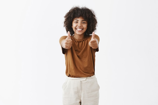 Fille afro-américaine lumineuse et joyeuse avec une coiffure afro en t-shirt marron élégant, tirant les mains vers avec les pouces vers le haut et souriant acclamations et soutien