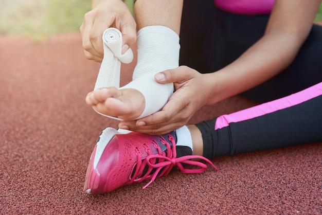 Fille afro-américaine mettant un bandage sur un pied blessé