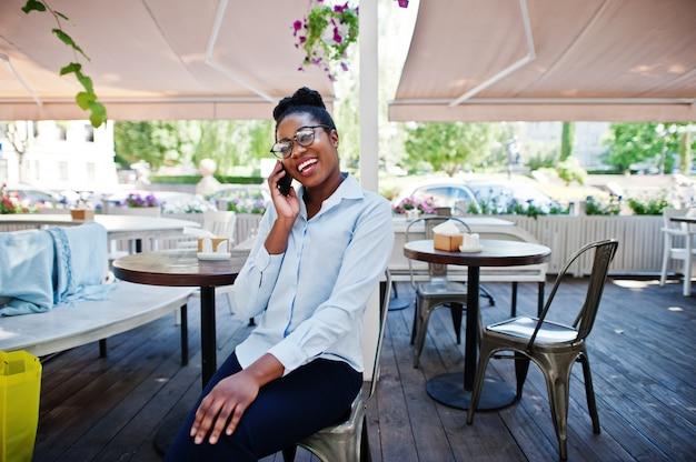 Fille afro-américaine porter dans des verres avec téléphone portable assis au café en plein air.