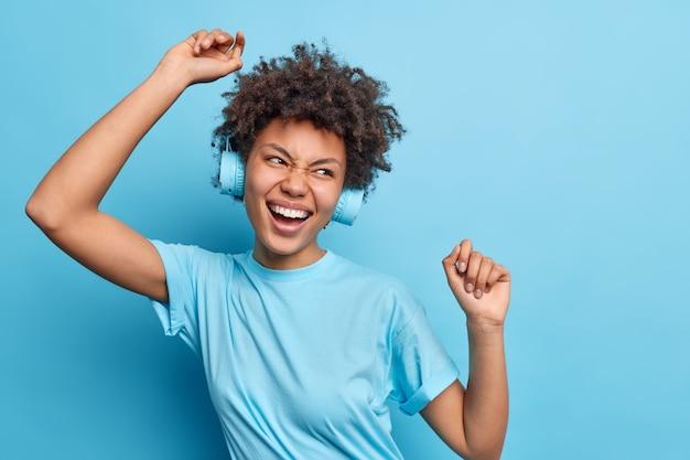 Une fille afro-américaine positive profite d'une bonne journée garde les bras levés a des poses amusantes sans soucis porte des écouteurs sur les oreilles pose de t-shirt décontracté contre le mur bleu. concept de divertissement de loisirs de personnes