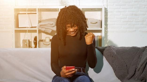 Une fille afro-américaine regarde un smartphone et devient heureuse