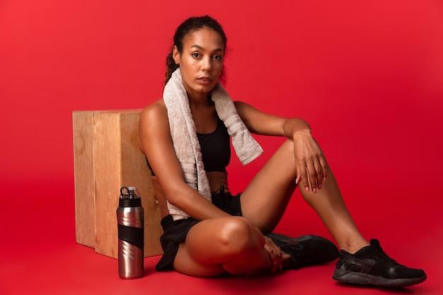 Fille afro-américaine en survêtement noir assis sur le sol avec une serviette et une bouteille d'eau, isolé sur mur rouge