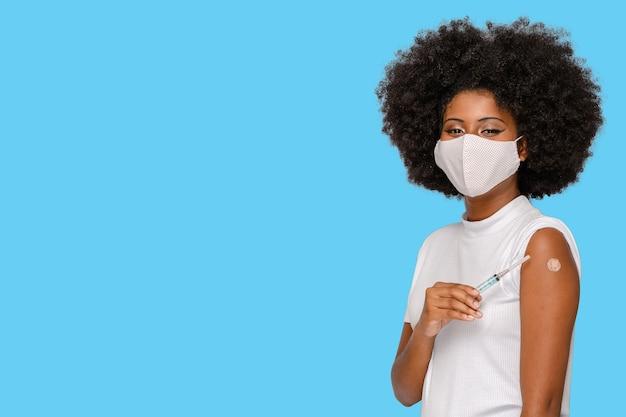 Une fille afro montre la marque du vaccin tenant la seringue montrant qu'elle a été vaccinée covid19