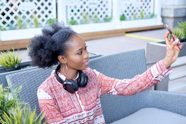 Fille afro noire en robe ethnique avec un casque assis dans un café en plein air, écouter de la musique et faire selfie sur smartphone