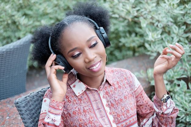 Fille afro noire en robe ethnique écoutant de la musique dans les écouteurs et souriant