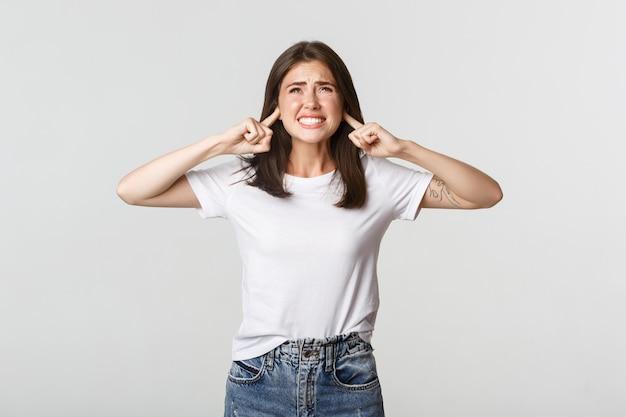 Une fille agacée et dérangée ferme les oreilles et se plaint d'un bruit affreux.