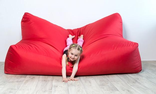 Fille d'âge préscolaire allongé sur un grand canapé rouge